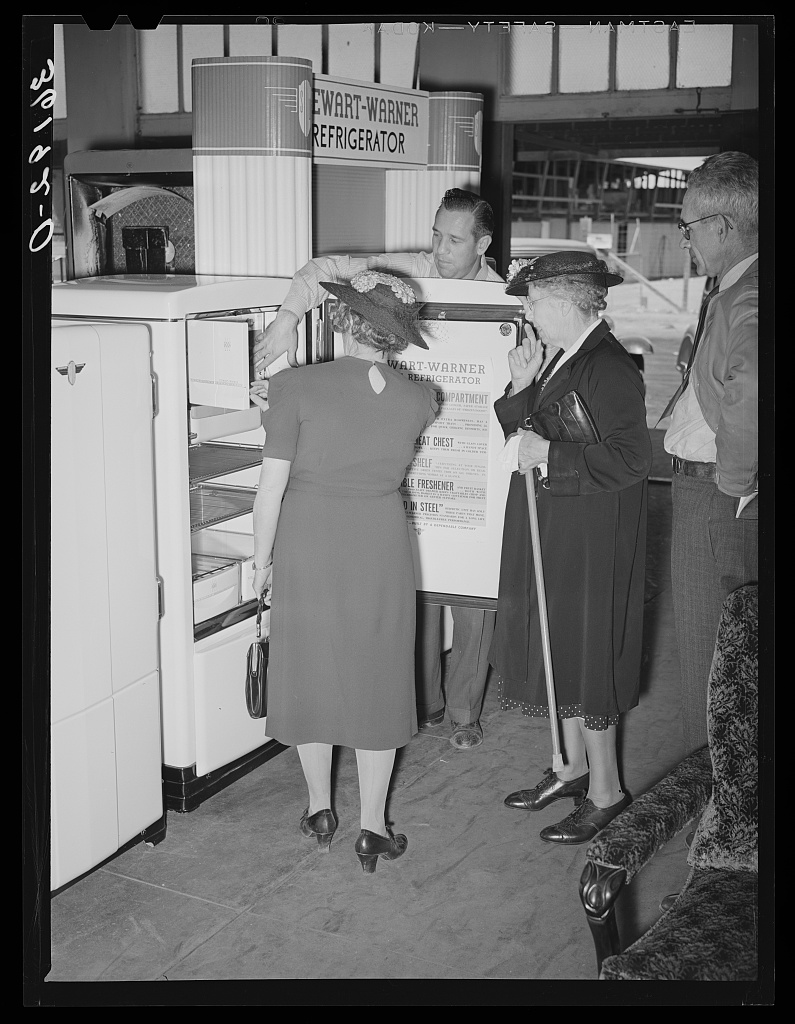 Salesman with refrigerator at co-op 1940
